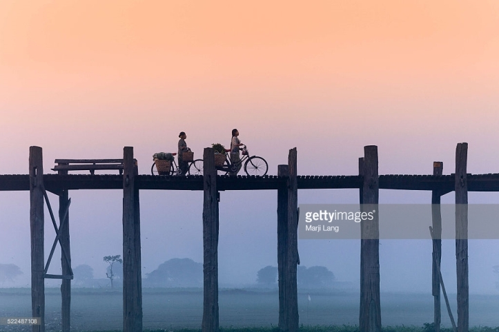 AMARAPURA, MANDALAY, MYANMAR, AMARAPURA, MANDALAY, MYANMAR - 2013/12/28: Cycling women on the U Bein bridge in Amarapura by a foggy and misty morning, near Mandalay, Burma (Myanmar). (Photo by Marji Lang/LightRocket via Getty Images)
