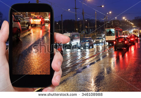 stock-photo-travel-concept-tourist-photographs-picture-of-night-car-traffic-on-street-in-rain-on-smartphone-346108988